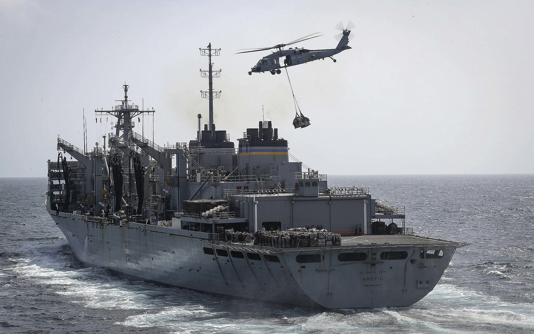 An MH-60S Sea Hawk helicopter transports cargo from the fast combat support ship USNS Arctic to the Nimitz-class aircraft carrier USS Abraham Lincoln during a replenishment-at-sea in the Arabian Sea (AP)