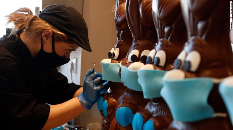 A cake shop employee in Athens Greece prepares chocolate Easter bunnies with face masks April 8 (Getty)