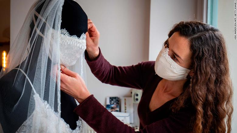 Designer Friedderike Jorzing adjusts a mannequin wearling a wedding dress with a face mask in her store in Berlin (March 30 Getty)