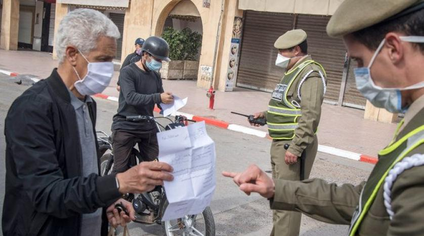 Moroccan police officers wearing protective masks check people at a roadblock during the coronavirus pandemic crisis. (AFP)