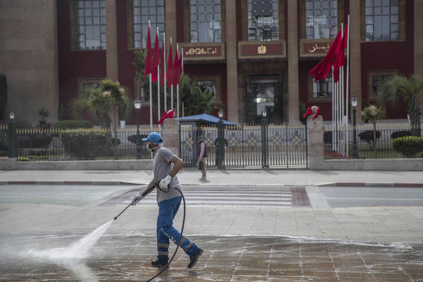 A worker disinfects a main avenue outside the parliament building in a bid to prevent the spread of coronavirus in Rabat (MAP)