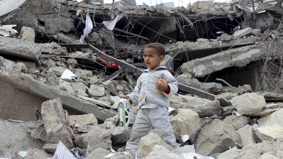 A boy walks as he collects toys from the rubble of a house destroyed by a recent air strike in Yemen's north-western city of Saada [Reuters]