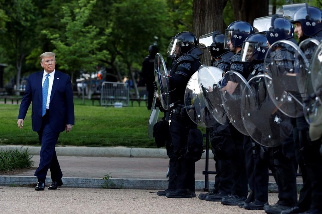 President Donald Trump walks past police in Lafayette Park after he visited outside St. John's Church across from the White House Monday, June 1, 2020 (Reuters)