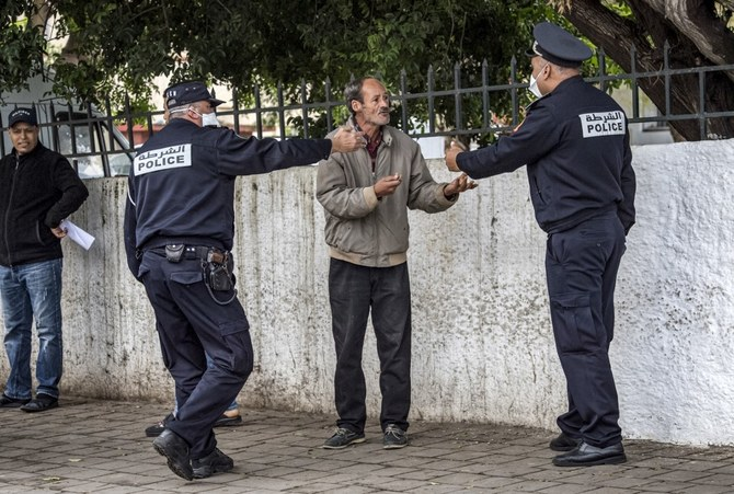 Policemen instruct a man to return home in Morocco's capital Rabat on March 22 2020 (AFP)